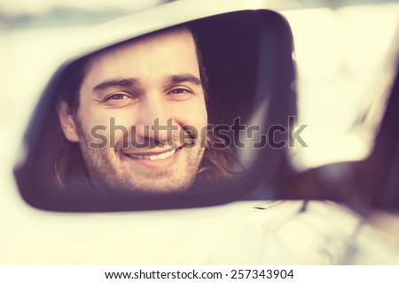 Happy young man driver looking in car side view mirror, making sure line is free before making a turn. Positive human face expression emotions. Safe trip journey driving concept