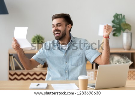 Happy young man excited feeling winner reading good news holding mail letter about getting job scholarship hired promoted, great exam test results, loan approval, receiving salary or taxes refund