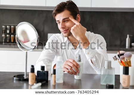 Happy young man filming his video blog episode about new cosmetic products while sitting at the kitchen table and applying make-up