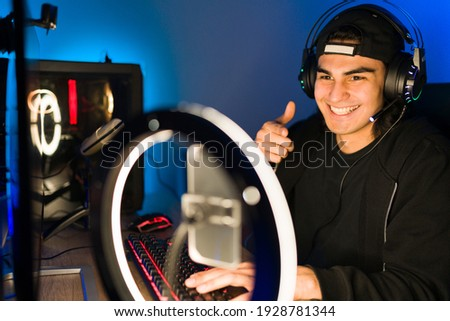 Happy young man giving a thumbs up to his viewers and friends during a live stream with a smartphone and a ring light. Smiling gamer playing a video game in a gaming computer Photo stock ©