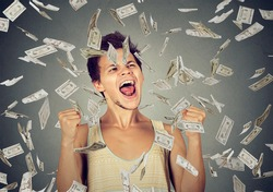 Happy young man going crazy screaming super excited. Ecstatic guy celebrates success under money rain falling down dollar bills banknotes isolated gray background. Financial freedom concept