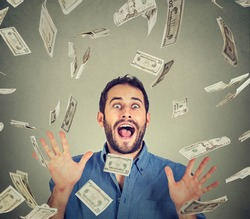 Happy young man going crazy screaming super excited. Portrait ecstatic guy celebrates success under money rain falling down dollar bills banknotes isolated gray background. Financial freedom concept