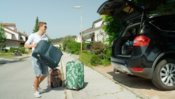 Happy young man holding a big suitcase is about to pack it in the trunk of the big black car parked in front of a suburban house. Cheerful Caucasian male tourist getting ready to go on fun holiday.