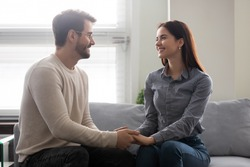 Happy young man holding attractive woman hands on couch. Smiling romantic couple enjoy time together. Beautiful family have fun time and enjoy romantic pastime.