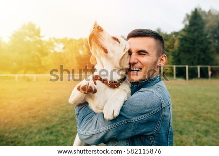 Happy young man holding dog Labrador in hands at sunset outdoors  #582115876
