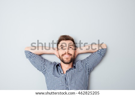 Happy young man holding hands behind head and looking up