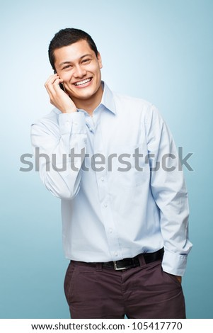 Happy young man holding mobile phone