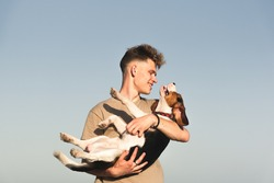 Happy young man holds his funny beagle dog, shot against clear blue sky with copy space. Lifestyle with pets, happy puppy owner, pedigree dog