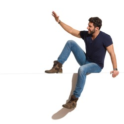 Happy young man in boots, jeans and blue shirt is sitting on a top, looking away and waving hand. Full length studio shot isolated on white.