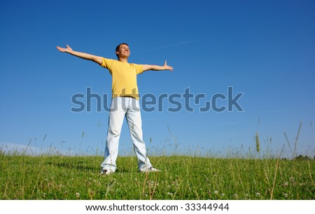 Happy young man in casual on the meadow, smile spreading his arms, summer sunny day