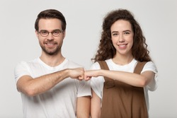 Happy young man in eyewear bumping fists with millennial smiling girl, isolated on grey white studio background. Family couple or friends come to mutual decision, friendship, relationship concept.