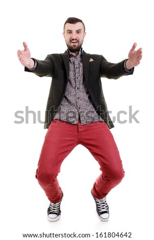 Happy young man in red jeans on a white background. Isolated.