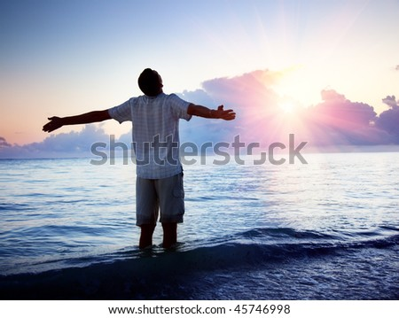 happy young man in sea and sunrise