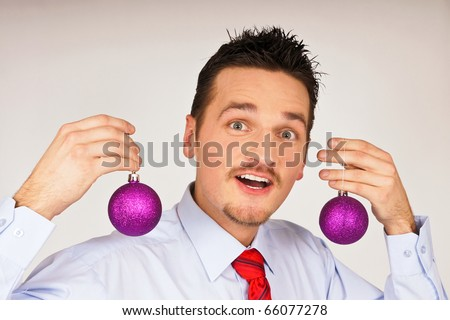 Happy young man in shirt and red tie shows violet Christmas Ornament