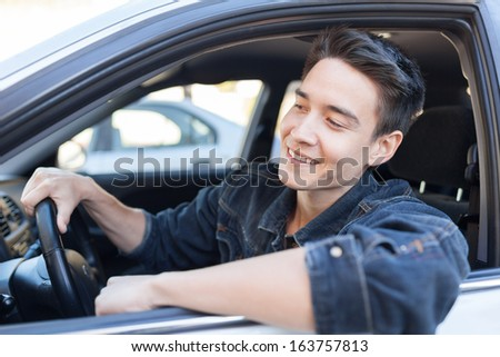 Happy young man in the car