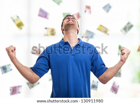 Happy young man in the middle of a rain of money