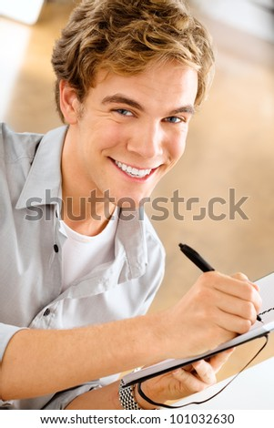 Happy young man is a student studying at home holding pen and sm
