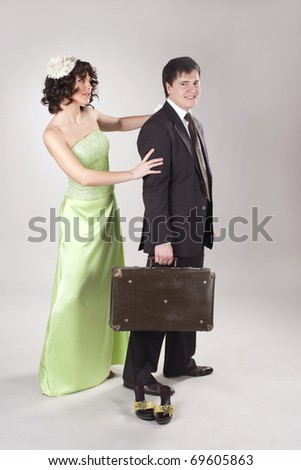 Happy young man is leaving his woman with small old suitcase