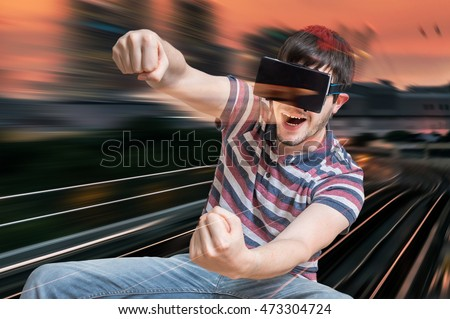 c6e188cd387a Happy young man is playing racing videogame in 3D virtual reality simulator  using headset. Driving