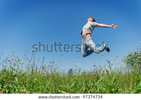 Happy young man jump on field