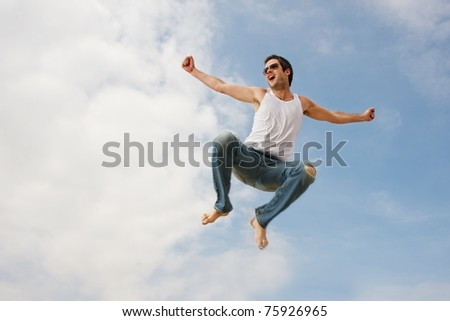 Happy young man jumping against blue sky