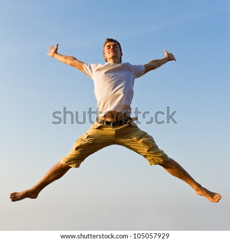 Happy young man jumping against blue sky background - stock photo