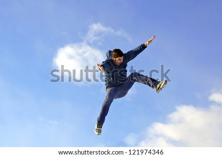 happy young man jumping on a sky background