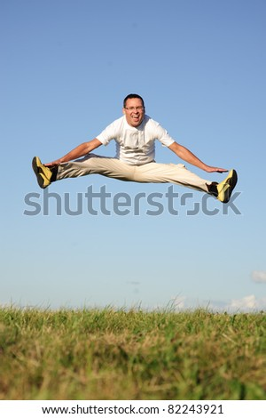 happy young man jumping on green field and do the splits in the air