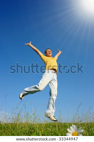 Happy young man jumping on the meadow, summer sunny day