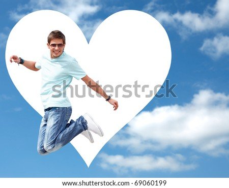 Happy young man jumping on the sky background. Big white heart shape behind him.