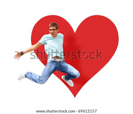 Happy young man jumping on the white background. Big red heart shape behind him. Isolated.