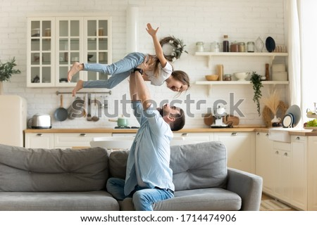 Happy young man lifting small preschool child daughter in air sitting on comfortable sofa in modern studio living room. Overjoyed kid girl having fun with handsome father, flying on hands at home.
