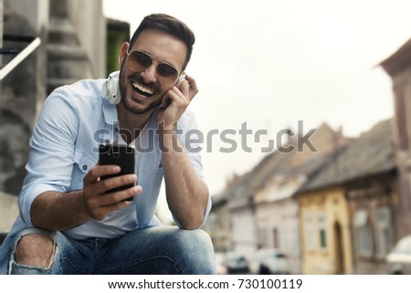 Happy young man listening music and smiling  #730100119