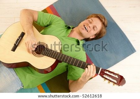 Happy young man lying on floor holding guitar, smiling in high angle view.