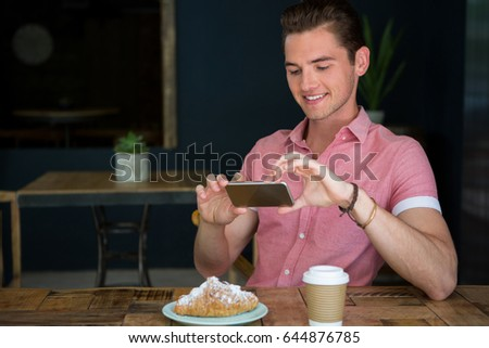 Happy young man photographing food on table in coffee shop