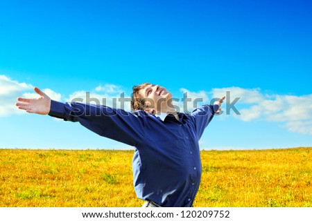 Happy Young Man raising his Hands in the Summer Field