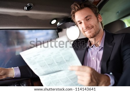 Happy young man reading newspaper in luxury car, smiling.