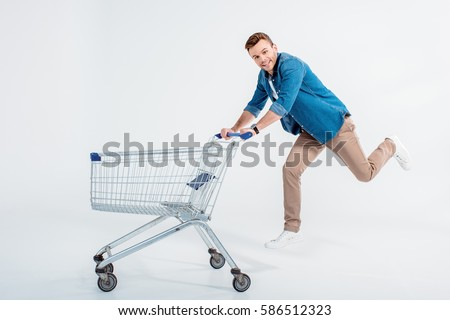 Happy young man running with shopping trolley and smiling at camera isolated on white