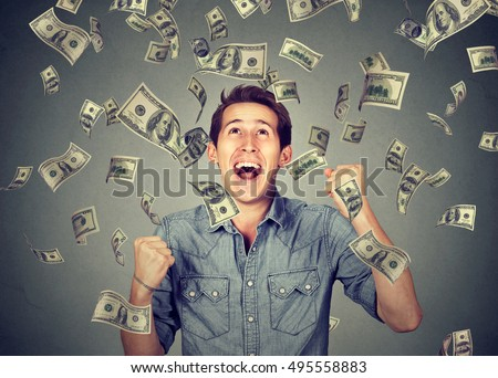Happy young man screaming super excited. Portrait ecstatic guy celebrates success under money rain falling down dollar bills banknotes isolated gray background. Financial freedom concept