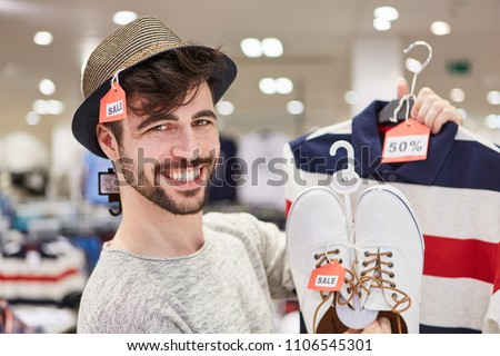 Happy young man shopping by fashion with 50% off discount