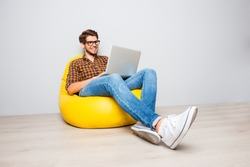 Happy young man sitting in yellow pouf  and using laptop.