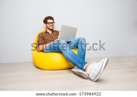 Happy young man sitting in yellow pouf  and using laptop. #573984922