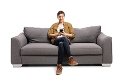 Happy young man sitting on a gray sofa and typing on a mobile phone isolated on white background