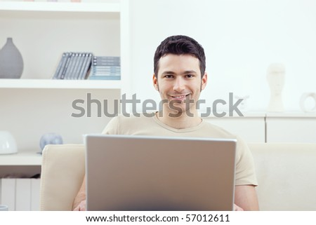 Happy young man sitting on couch at home using laptop computer, smiling.