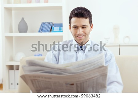 Happy young man sitting on couch reading newspaper at home, smiling.