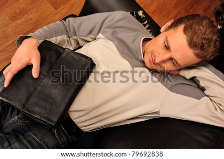 Happy young man sitting on sofa at home and holding handbag