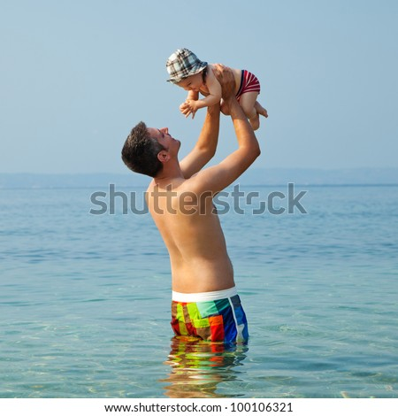 Happy young man standing in the sea and holding a smiling 9 months old baby