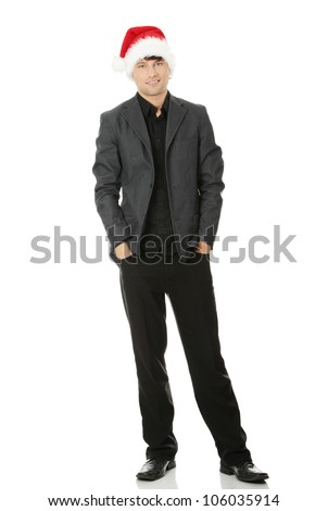 Happy young man standing, wearing suit and the Santa Claus hat. Isolated on the white background.