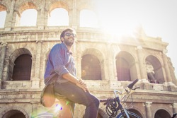 Happy young man tourist on a bike wearing blue shirt and sunglasses at colosseum smiling in Rome on sunny day. Lens flare.