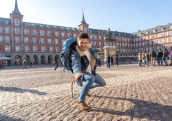 Happy young man traveling around Europe having fun pretending to surf in Plaza de Espa–a, Madrid, Spain. In People Vacations, adventure, backpacking, student lifestyle and surfing the world concept.